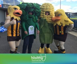 Postcard showing Hawkes player, person in broccoli costume, person in corn costume and person dressed up as Hawk mascot